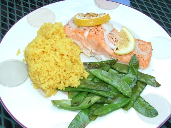 Salmon with dill sauce, sauteed pea pods, and yellow rice.